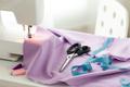 sewing machine, scissors, tape measure and fabric
