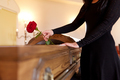 woman with red roses and coffin at funeral - PhotoDune Item for Sale