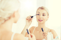 woman with mascara applying make up at bathroom - PhotoDune Item for Sale