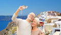 senior couple with camera travelling in santorini - PhotoDune Item for Sale
