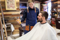 barber showing hair styling spray to male customer - PhotoDune Item for Sale