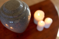 cremation urn and candles burning on table - PhotoDune Item for Sale