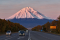 Cars Drive Along the Road On Background Volcano at Sunset Sun - PhotoDune Item for Sale