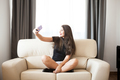 Beautiful gorgeous young woman taking a selfie in the room - PhotoDune Item for Sale