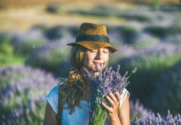 Young girl wearing straw hat with bouquet of lavender flowers - Stock Photo - Images