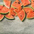Juicy watermelon pieces over concrete stone background, square crop