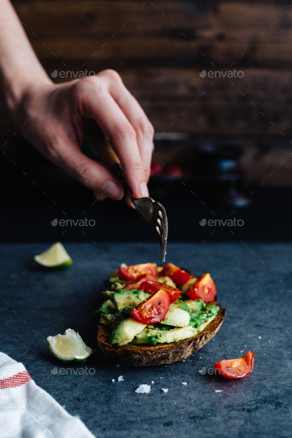 Eating Avocado and Tomato on Sourdough Bread - Stock Photo - Images
