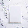 Blank frame and white flowers over marble table - PhotoDune Item for Sale