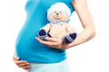 Pregnant woman holding fluffy teddy bear with cap for kids, expecting for baby