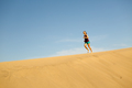 Woman running barefoot on sand desert dunes