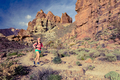 Woman trail ultra running in mountains with backpack