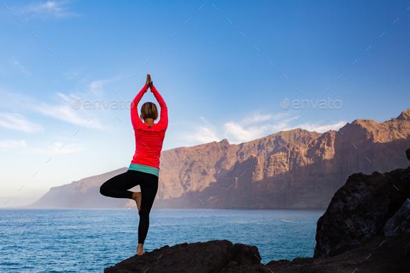 Woman meditating in yoga vrksasana tree pose - Stock Photo - Images