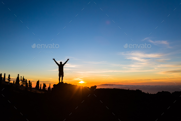 Man hiker silhouette with arms outstretched enjoy mountains - Stock Photo - Images