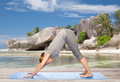 woman doing yoga dog pose on beach