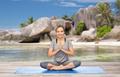 woman doing yoga meditation in lotus pose on beach