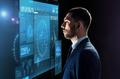 businessman looking at virtual screen over black