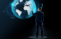 businessman in suit touching earth globe hologram
