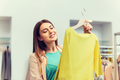 happy young woman choosing clothes in mall - PhotoDune Item for Sale