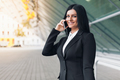 Successful business woman with mobile phone in an urban setting