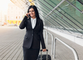 Young business woman with mobile phone and suitcase in urban setting