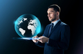 businessman with tablet pc and earth projection