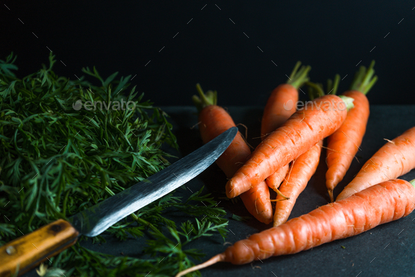 Orange carrots, leaves and a knife on a dark blue background - Stock Photo - Images