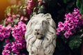 Small concrete sculpture of lion among flowers