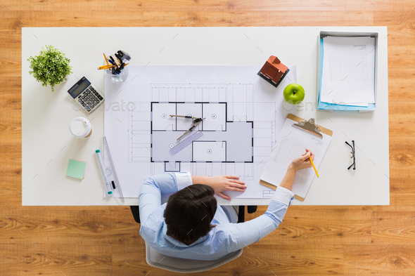 architect with blueprint writing to clipboard - Stock Photo - Images