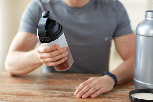 close up of man with protein shake bottle and jar - Stock Photo - Images