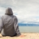 Cinemagraph - Man or Woman Is Sitting in a Hoodie on the Beach. Back View - VideoHive Item for Sale