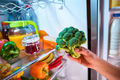 Woman takes the broccoli from the open refrigerator.