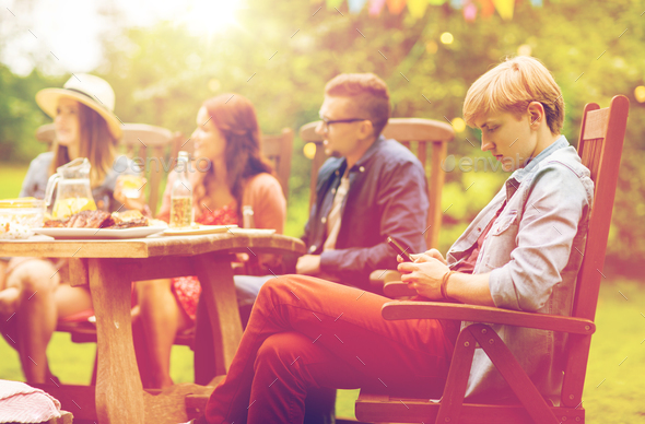 man with smartphone and friends at summer party - Stock Photo - Images