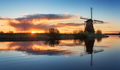 Landscape with traditional dutch windmills at colorful sunrise,