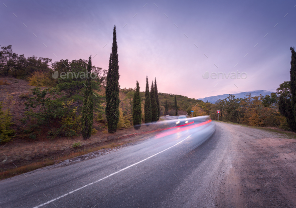 Mountain road with blurred cars in motion at sunset - Stock Photo - Images
