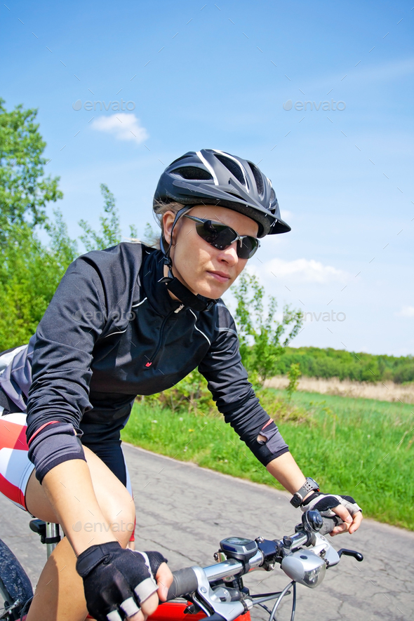 Woman riding on bicycle on summer day - Stock Photo - Images