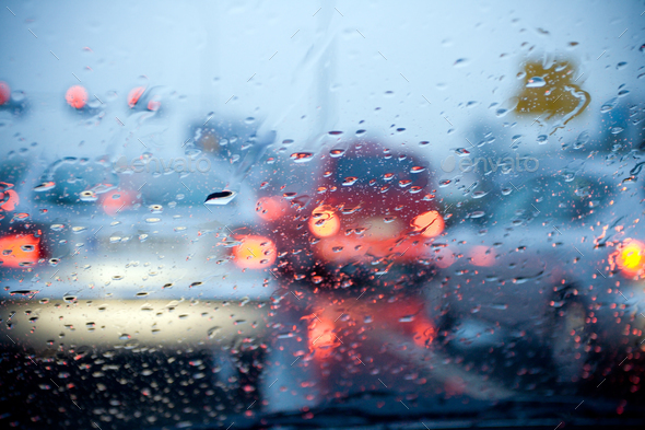 Car driving in a rain storm with blurred red lights - Stock Photo - Images