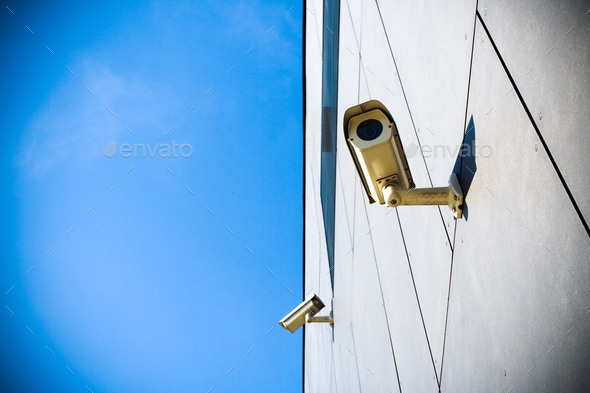 Security camera over blue sky - Stock Photo - Images