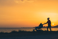 Mother walking on beach with stroller enjoying motherhood