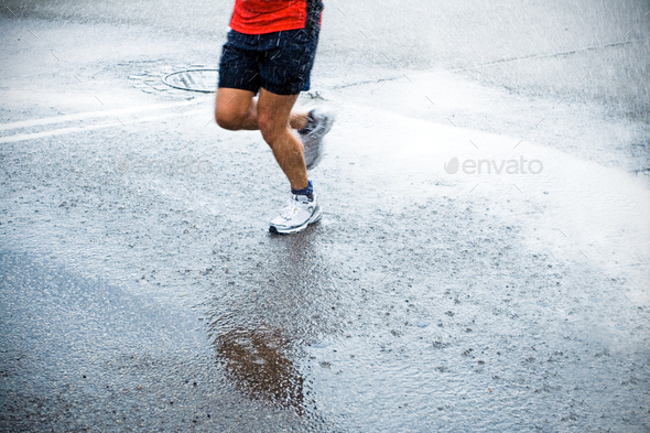 Marathon runner in rain on city street - Stock Photo - Images