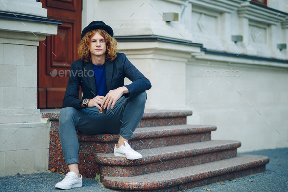 Red haired hipster man sitting on stairs thinking - Stock Photo - Images