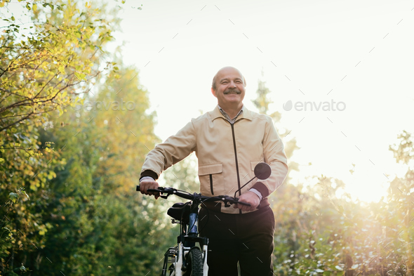 Senior man go for a walk with bike in countryside - Stock Photo - Images