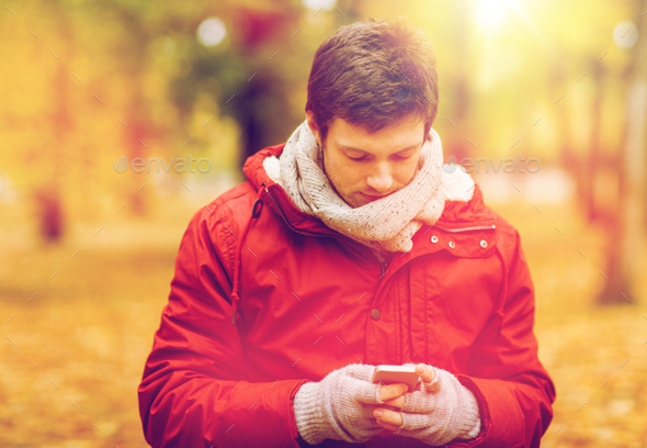 young man with smartphone walking at autumn park - Stock Photo - Images