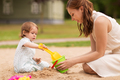 happy mother with baby girl playing in sandbox