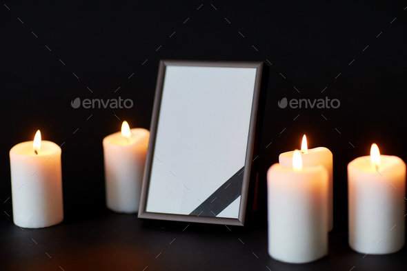 black ribbon on photo frame and candles at funeral - Stock Photo - Images