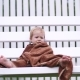 a Little One-year-old Girl, Wrapped in a Towel, with a Dirty Face, Lonely Sitting on a Swing in the - VideoHive Item for Sale