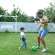 Dad with a Four-year-old Son Playing Football in the Yard on a Green Lawn - VideoHive Item for Sale