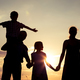 Happy family standing on the field at the sunset time. - PhotoDune Item for Sale