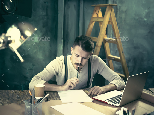 Portrait of a bearded businessman who is working with his notebook at loft studio. - Stock Photo - Images
