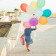 Girl running on the stairs holding colorful balloons and childis - PhotoDune Item for Sale