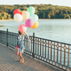 Cheerful girl holding colorful balloons and childish suitcase wa - PhotoDune Item for Sale